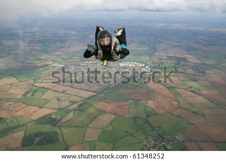 Skydiver in freefall on a sunny day - stock photo