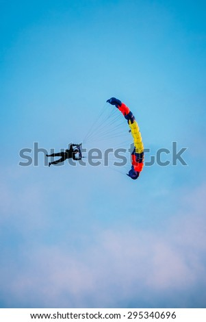 Skydiver On Colorful Parachute In Sunny Clear Sky. Active Hobbies - stock photo