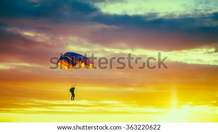 Skydiver On Colorful Parachute In Sunny Sunset Sky. Active Hobbies - stock photo