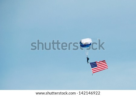Skydiver streaming the American flag while landing - stock photo