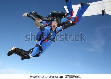 Skydiver waves at the camera - stock photo