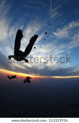 Skydivers at sunset - stock photo