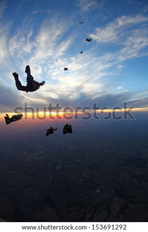 Skydivers at sunset
