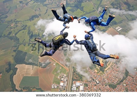 Skydivers make a star formation above the clouds. - stock photo