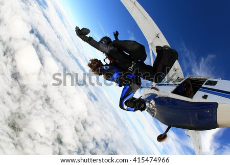 Skydiving tandem jumping from the plane - stock photo
