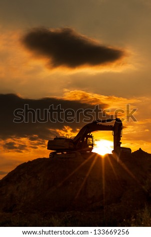 skyline excavator with colored sunset - stock photo