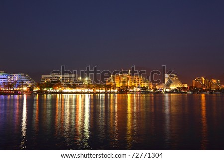 Skyline of Eilat at night: coastline, beach, hotels, promenade, mountains and bay. Eilat is located on Red Sea in Israel, Gulf of Aqaba.