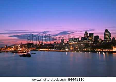 Skyline of the City of London at dusk. Thames River on foreground, copy space in the sky