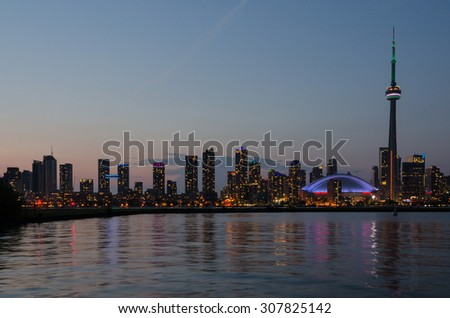 Skyline of Toronto over Ontario Lake after sunset - stock photo