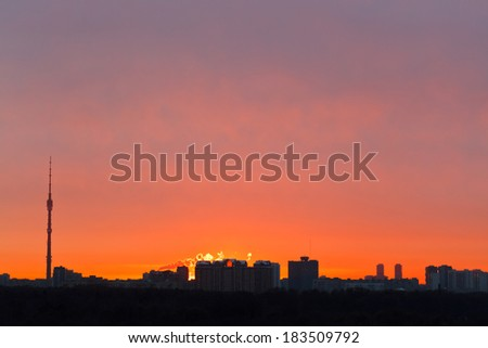 skyline with early red dawn over city in spring morning - stock photo