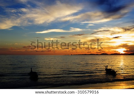 Skyscape, scenic sunset on Andaman sea with silhouette of boats, Ao Nang beach, Thailand.