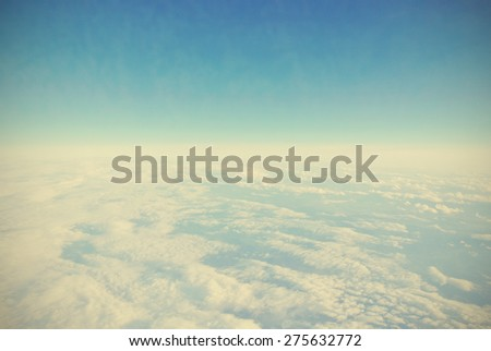 Skyscape - sky landscape with blue sky and white fluffy clouds seen from an airplane. Clouds texture. Image filtered in faded, washed out, retro style with dark vignette. - stock photo