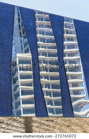 Skyscraper in construction reflected in the mirrors of a blue wall - stock photo