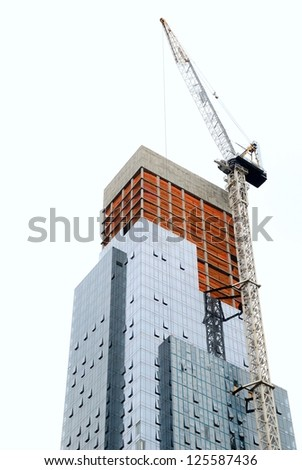 Skyscraper under construction with crane on white background. - stock photo
