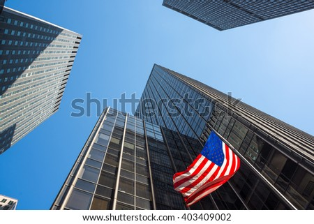 Skyscrapers and an American flag waving in mid-town Manhattan. - stock photo