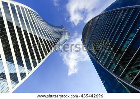 Skyscrapers, modern business office buildings in commercial district, architecture raising to the blue sky with white clouds, bottom view  - stock photo