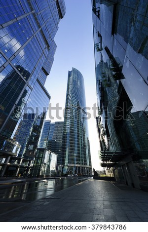 Skyscrapers, modern business office buildings in commercial district, bottom view, city architecture raising to the blue sky - stock photo