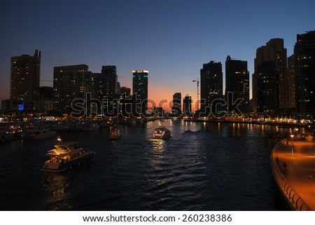 Skyscrapers of Dubai Marina captured in the dusk. Dubai Marina is an artificial canal city, carved along a two mile stretch of Persian Gulf shoreline. - stock photo
