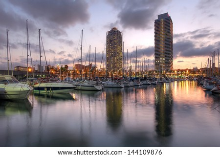 Skyscrapers towering over the marina in Port Olimpic (Olympic Harbor), Barcelona, Spain at sunset.