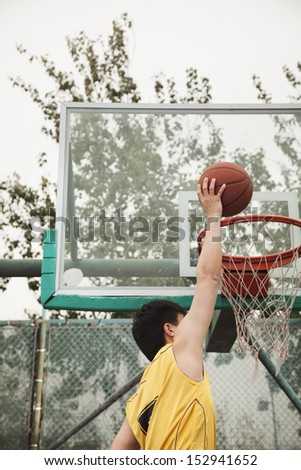 Slam dunk by young man - stock photo