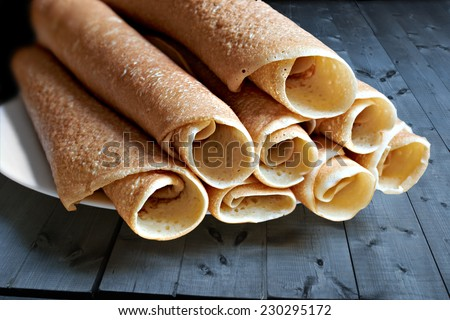 slapjack, pancakes, rolled and laid the slide on the plate - stock photo