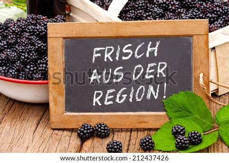 Slate blackboard with the Germans words: Frisch aus der Region (Fresh from the region), in front of ripe blackberries on a rustic wooden table - stock photo