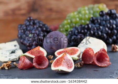 Slate board with blue cheese, blue and green grapes, figs, walnuts and salami - stock photo