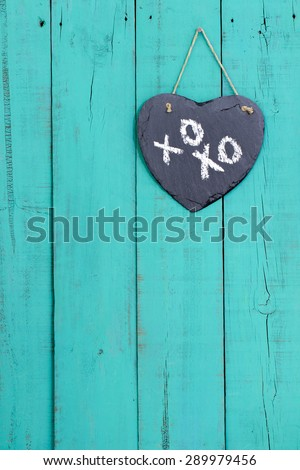 Slate heart with XOXO, hugs and kisses, hanging from rope on rustic antique teal blue wooden background - stock photo