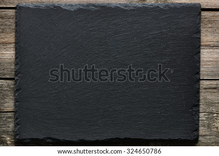 Slate over old wooden background - stock photo