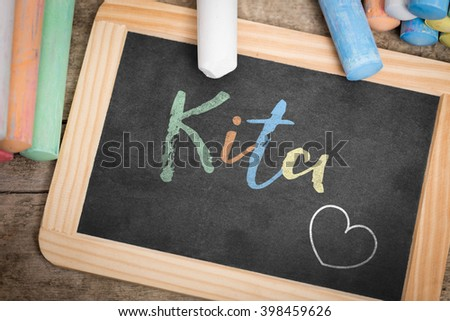 Slate with german word Kita, which means Kindergarten, colorful crayon on wooden Table, flat lay
