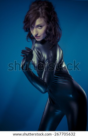 Slave, sexy brunette in black latex bodysuit tight and wild poses - stock photo