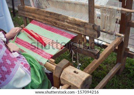 Slavic vintage wooden loom at work, horizontal shot - stock photo