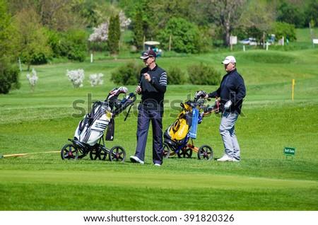SLAVKOV-AUSTERLITZ NEAR BRNO, CZECH REPUBLIC- APRIL 29, 2015: Two men walking with golf trolleys at spring green lawn in Slavkov - Austerlitz near Brno, Czech Republic - stock photo