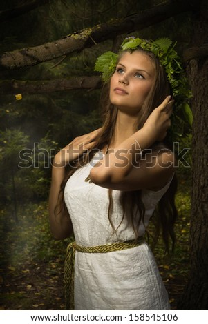 Slavonic girl in the traditional suit in the deep forest