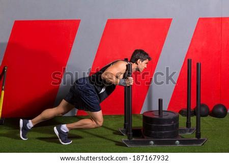 sled push man pushing weights workout exercise at gym - stock photo