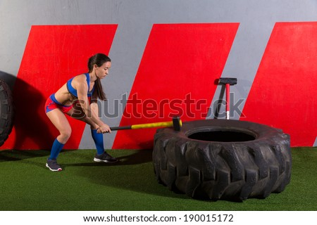 Sledgehammer Tire Hits woman workout at gym with hammer and tractor tire - stock photo