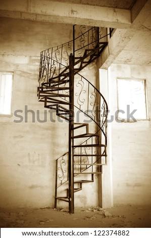 Sleek metal spiral staircase, modern architectural interior decoration. - stock photo