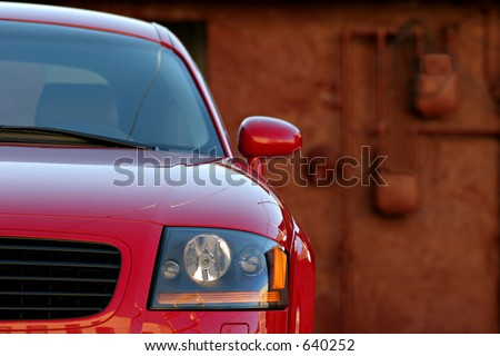 sleek sportscar - parked behind an old decaying building. focus on headlights with nice blurred background - stock photo