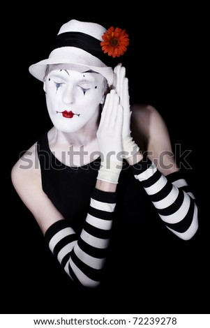 Sleep theatrical clown in a white hat and striped gloves on a black background - stock photo