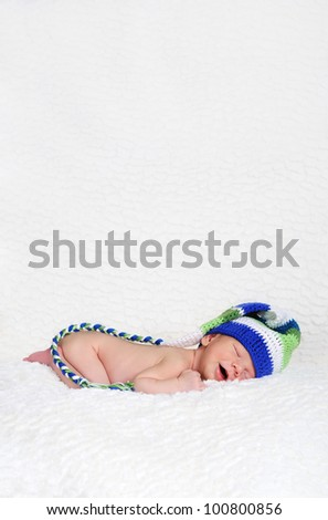 Sleeping and smiling newborn wearing a knitted winter hat - stock photo