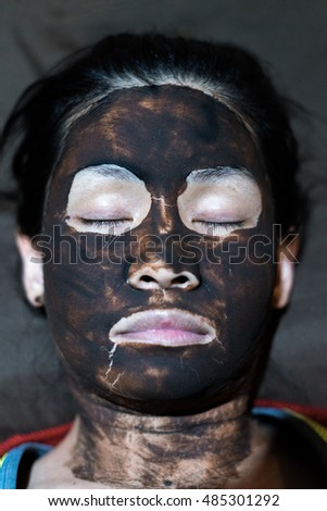Sleeping Asian female face covered with mud facial mask.