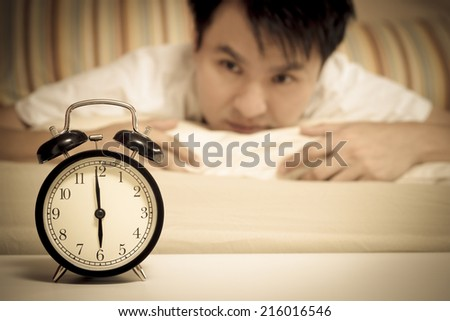 sleeping asian young male disturbed by alarm clock early morning on bed - stock photo