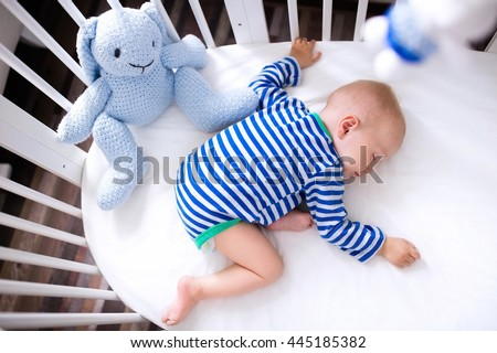 Sleeping baby and his toy in white crib. Nursery interior and bedding for kids. Cute little boy napping in bassinet. Kid taking a nap in white bedroom. Healthy child in bodysuit pajamas. - stock photo