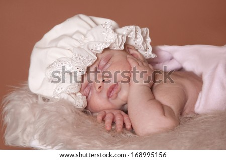 Sleeping baby girl with a vintage bonnet on her head. - stock photo