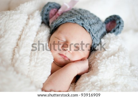 Sleeping baby in a blanket and hat - stock photo