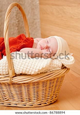 sleeping baby in a wicker basket - stock photo