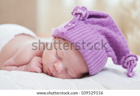 sleeping baby in an amusing violet hat - stock photo