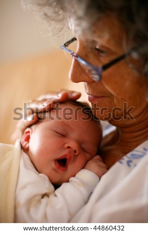 Sleeping baby in grand mothers arms - stock photo