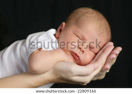 Sleeping baby in Mother's Hands - stock photo