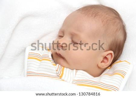 Sleeping baby on back in sleeping bag - stock photo